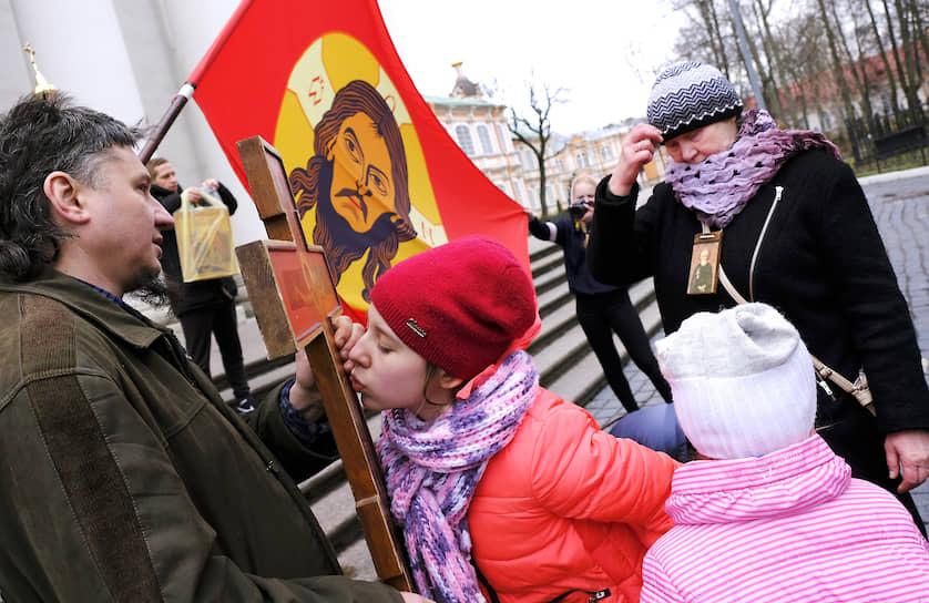 Верующие целуют распятие после несогласованного пасхального крестного хода по Невскому проспекту организованного бывшим священником Артемием Скрипиным