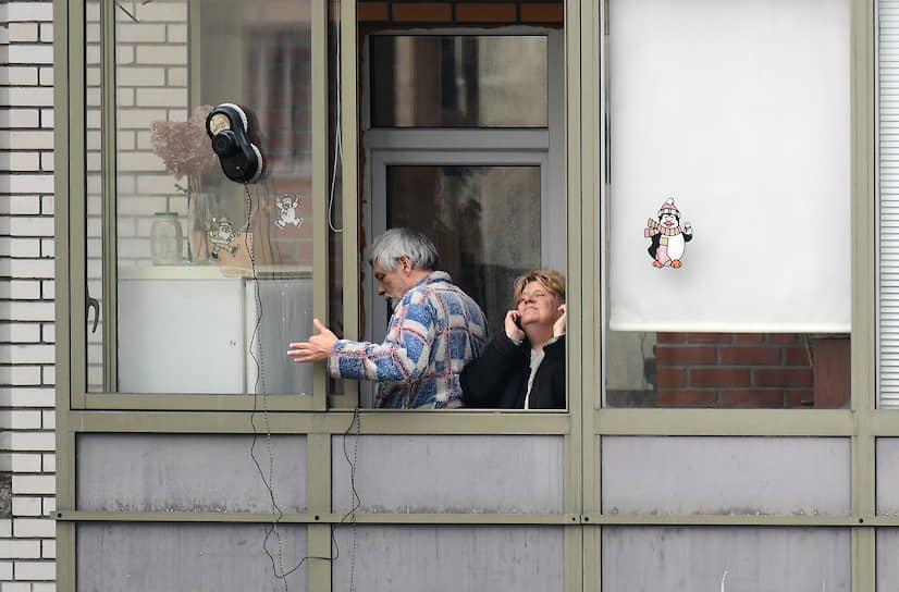 Мужчина и женщина во время самоизоляции на лоджии своей квартиры