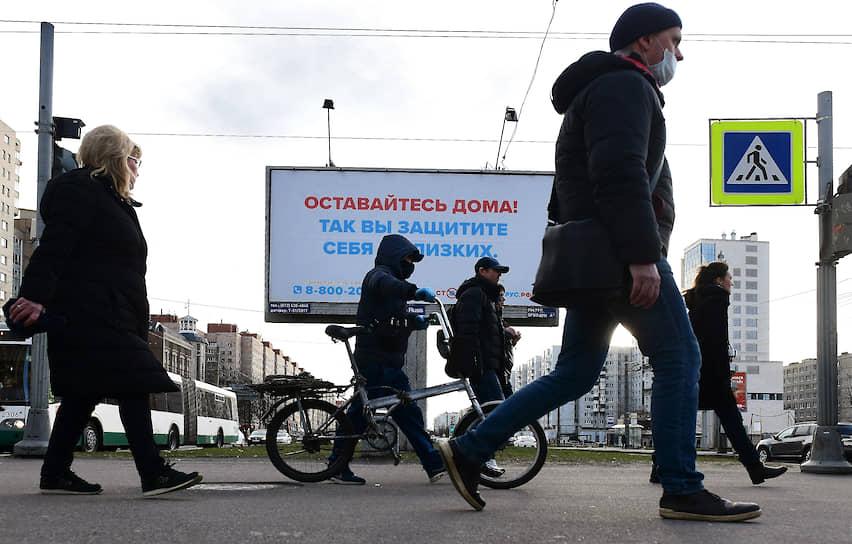 """Пешеходы идут под билбордом с социальной рекламой: """"Оставайтесь дома! Так вы защитите себя и близких."""""""