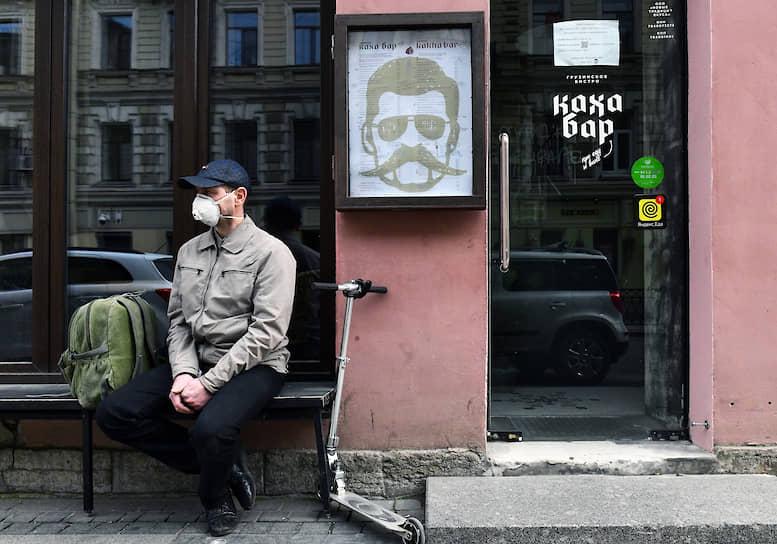 """Мужчина в маске сидит возле закрытого из-за эпидемии заведения """"Каха-Бар"""""""