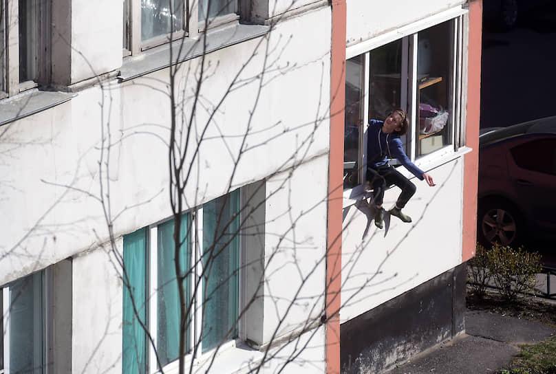 Подросток сидит на окне первого этажа многоквартирного дома во время режима самоизоляции