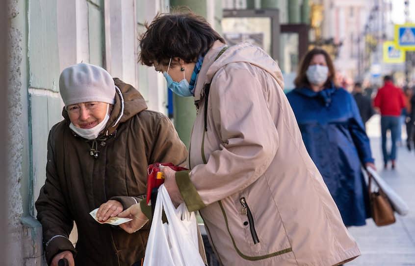 Женщина дает деньги пожилой женщине на улице