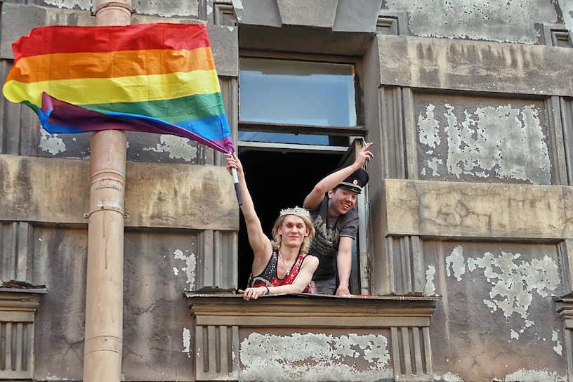 Представители ЛГБТ-сообщества в окне с флагом ЛГБТ