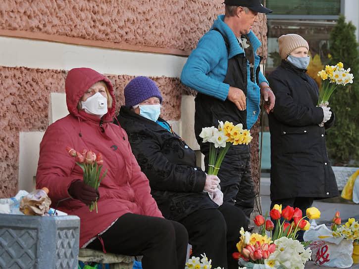 Пожилые женщины в медицинских масках продают весенние цветы