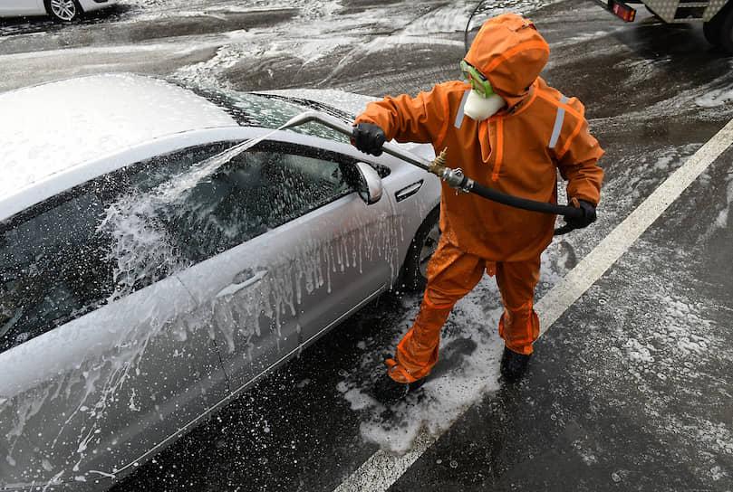 Сотрудники службы дезинфекции обрабатывает автомобиль на территории Городской больницы Святого Георгия