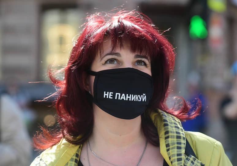 Женщина в маске в центре города