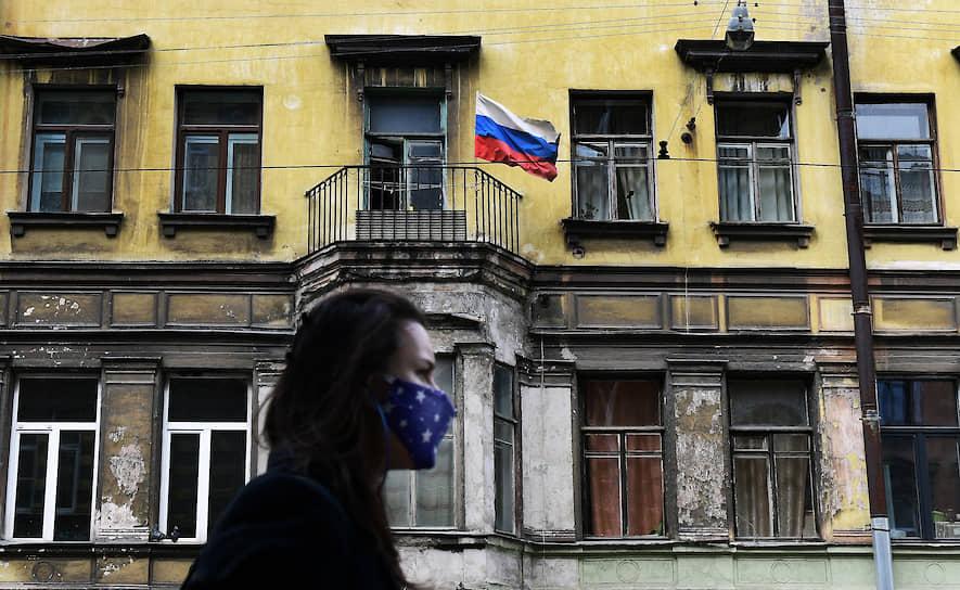 Девушка в маске на фоне российского флага на Колокольной улице
