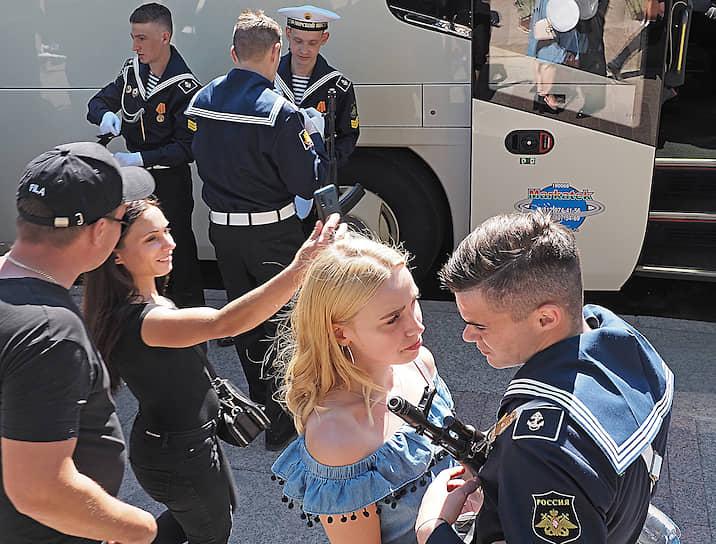 Военные моряки с девушками после окончания парада.