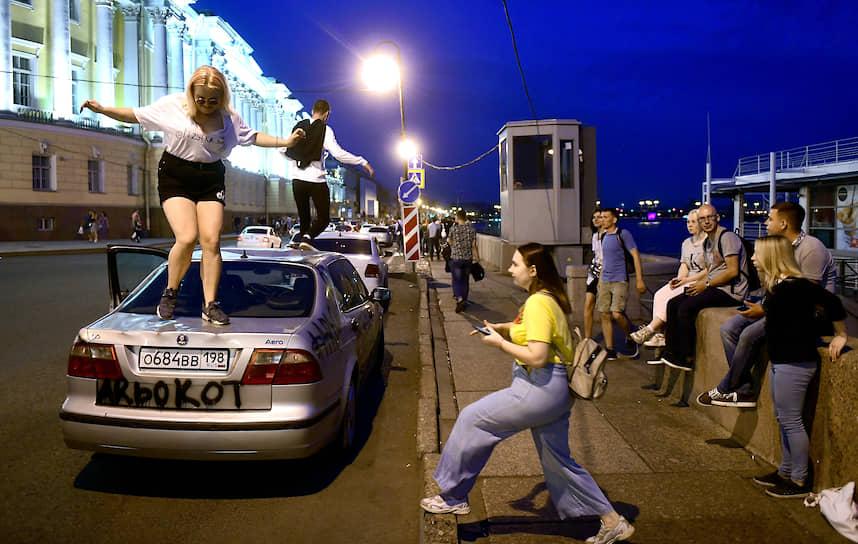Молодые люди на крыше автомобиля