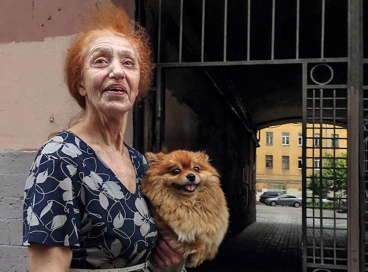 Женщина с собачкой у входа во двор