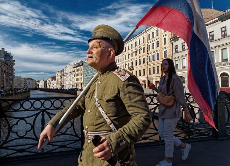 Мужчина в военной форме царской русской армии идет с флагом  по Невскому проспекту в День России