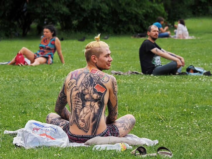 Молодой человек с татуировкой на лужайке в парке в центре города
