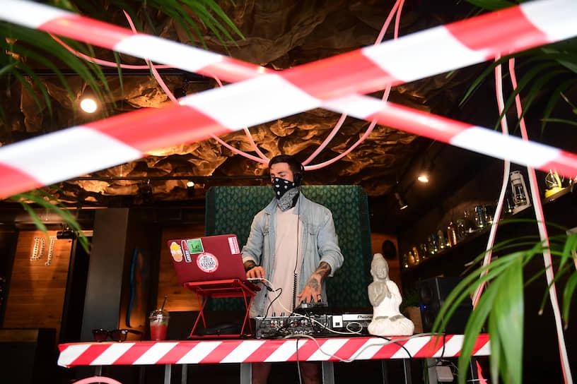 Диджей во время работы в закрытом, в связи с эпидемией коронавируса, помещении ресторана