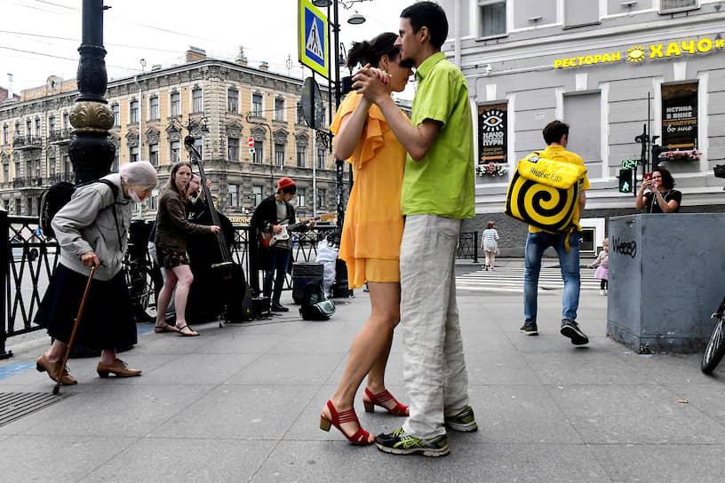 Молодые люди танцуют под музыку уличных музыкантов на улице Рубинштейна во время режима рекомендованной самоизоляции из-за опасности распространения коронавирусной инфекции COVID-19