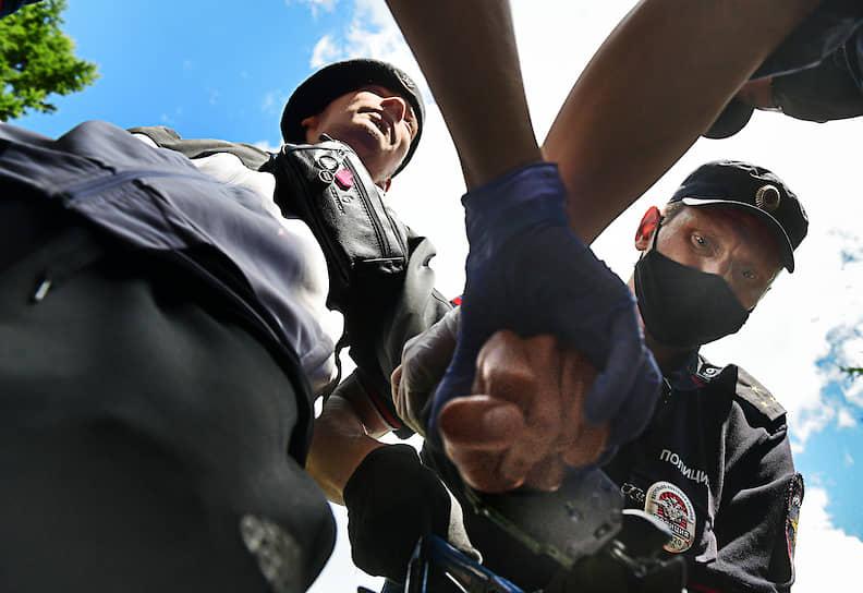 Сотрудники полиции пытаются снять наручники с активиста, который приковал себя к ограде в знак протеста против решения суда по делу Юлия Бояршинова и Виктора Филинкова