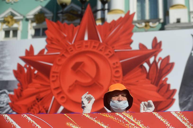 Женщина в маске на трибуне для ветеранов перед началом парада посвященного 75-й годовщине Победы в Великой Отечественной войне