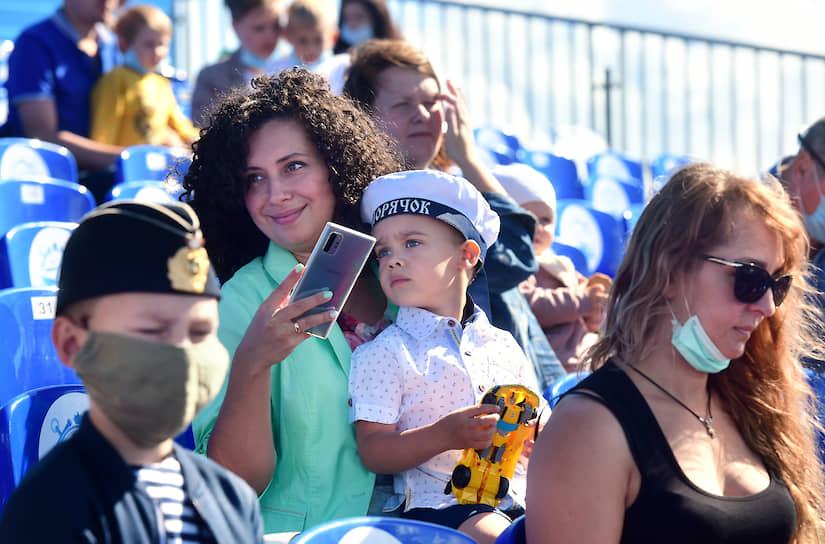 Военно-морской парад в честь Дня Военно-морского Флота (ВМФ) России в Кронштадте. Жанровая фотография. Зрители на зрительской трибуне перед началом парада