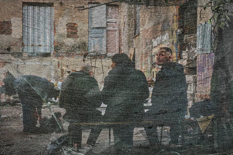 Мужчины сидят на лавочке во дворе полуразрушенного дома за оградительной строительной сеткой