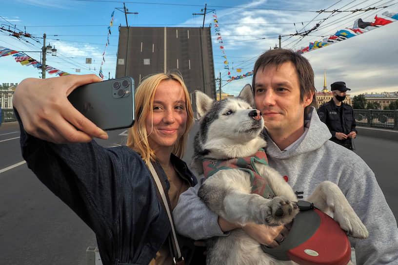 Молодые люди делают селфи с собакой на фоне разведенного Дворцового моста во время репетиции Главного военно-морского парада ко Дню Военно-морского флота