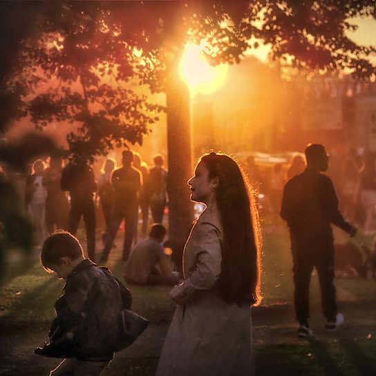 Горожане гуляют в парке в закатном солнце в День ВМФ