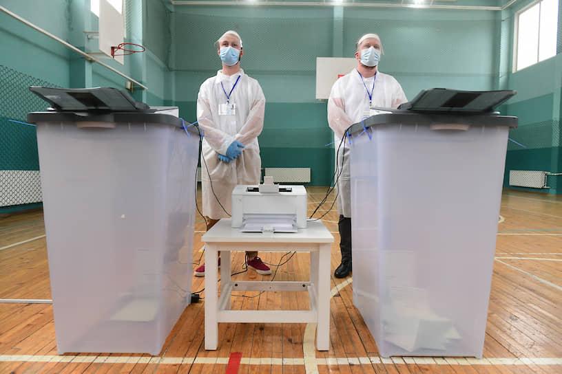 Сотрудники участковой избирательной комиссии в защитной одежде на избирательном участке в день голосования за поправку в Конституцию РФ