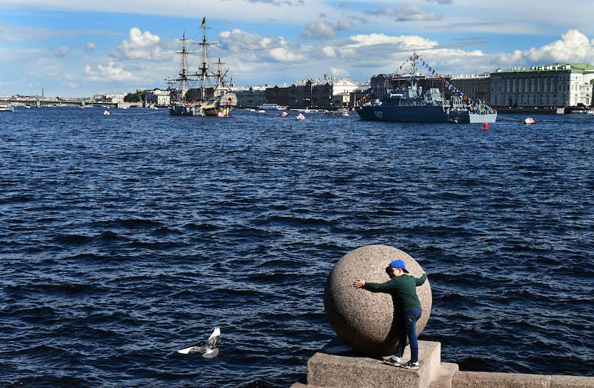 Мальчик обнимает гранитный шар на Стрелке Васильевского острова на фоне военных кораблей в акватории Невы