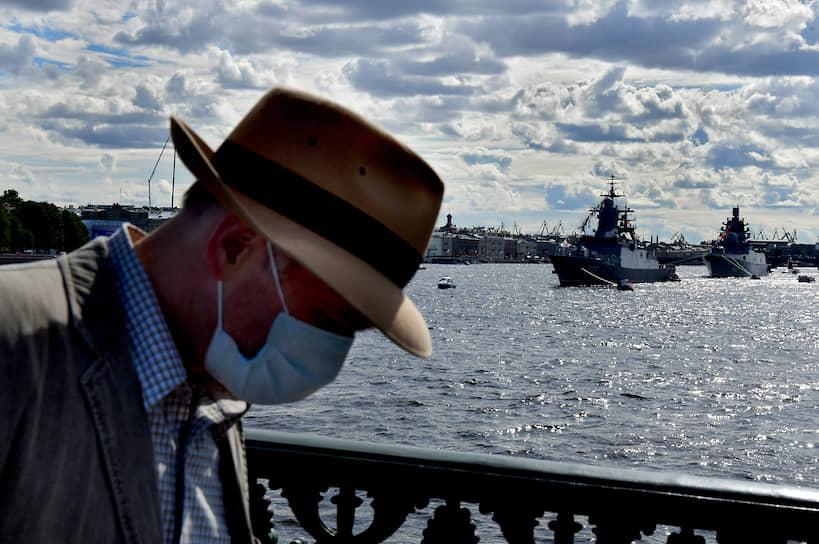 Мужчина в шляпе и медицинской маске на Дворцовом мосту на фоне военных кораблей в акватории Невы