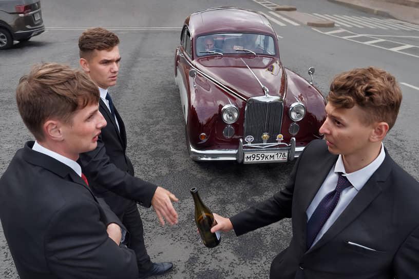 Молодые люди, гости на свадьбе возле свадебной машины