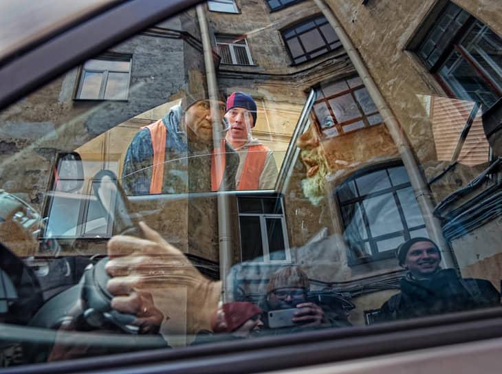 Водитель за рулем автомобиля позирует фотографу
