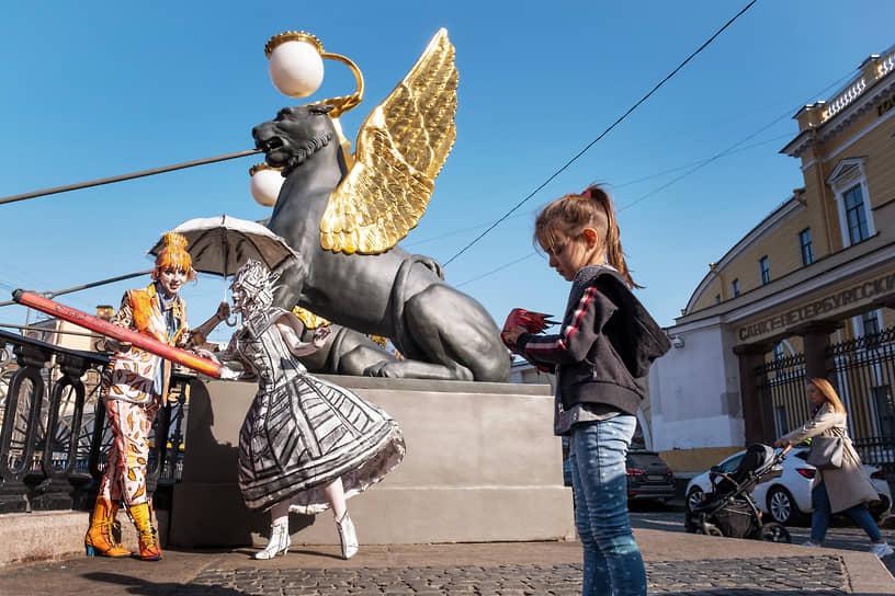 Юная художница Елизавета Анисимова позирует вместе с моделью у Банковского моста в Санкт-Петербурге