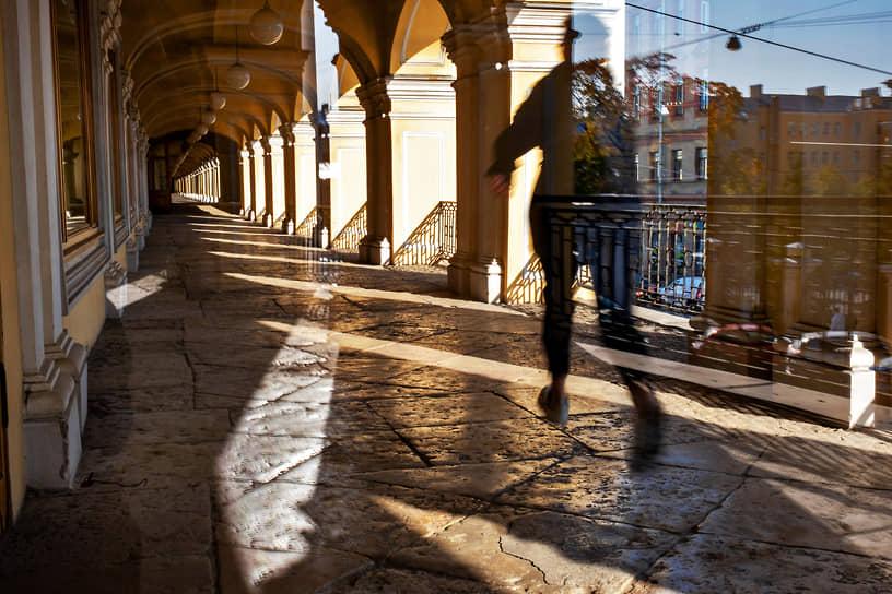Отражение человека идущего по второму этажу галереи Гостиного двора