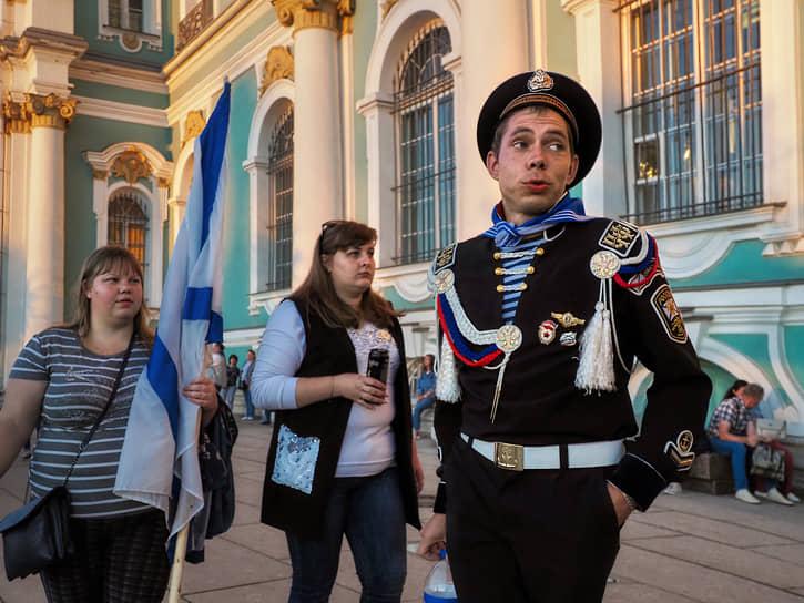 Мужчина в форме ВМФ и девушка с Андреевским флагом после окончания парада в честь Дня Военно-морского флота