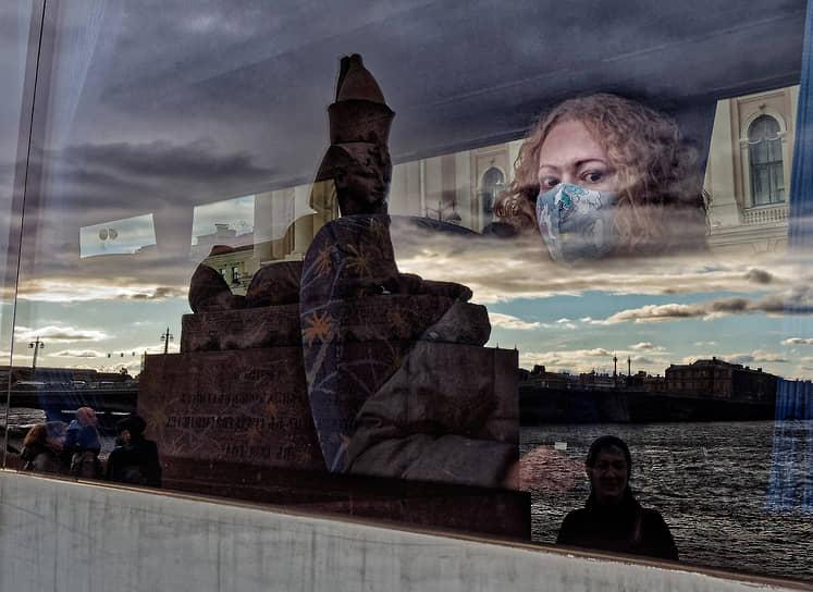 Девушка в маске в окне туристического автобуса