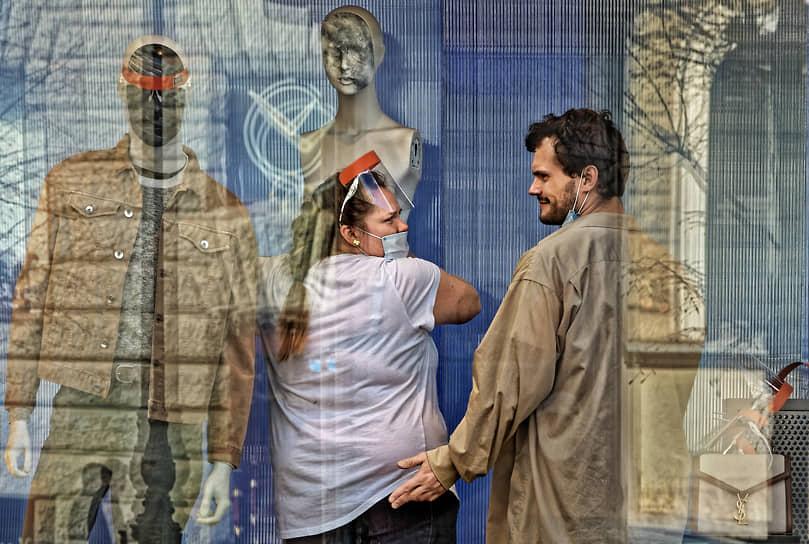 Мужчина и женщина в медицинских масках оформляют витрину магазина