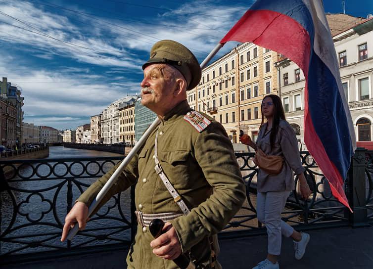 Пожилой мужчина в военной форме царской русской армии идет по Невскому проспекту с флагом России