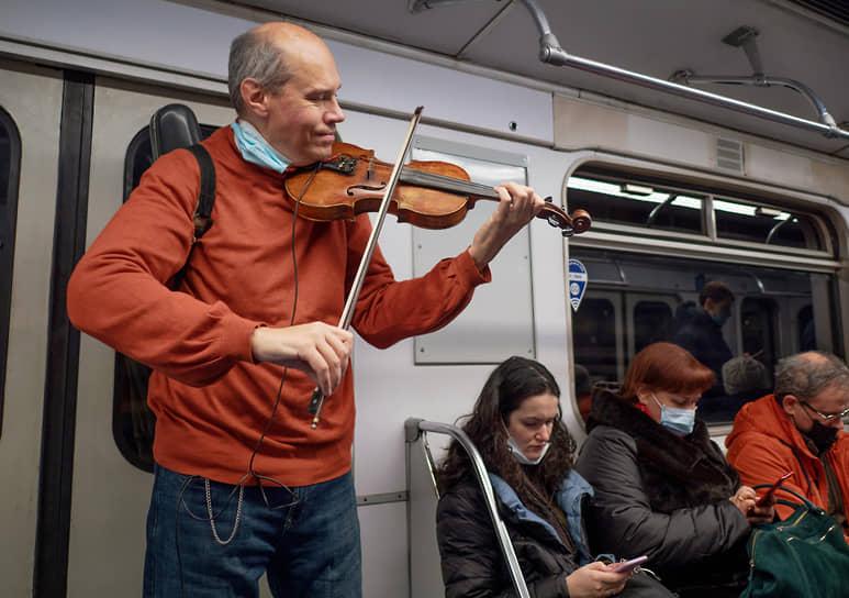 Мужчина играет на скрипке в вагоне метро