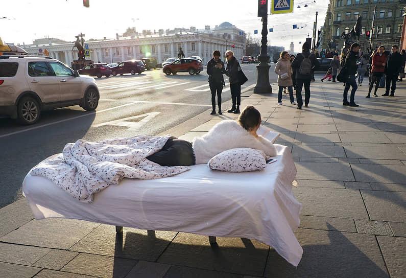 Девушка лежит в постели и читает книгу на Невском проспекте, призывая к добровольной самоизоляции из-за пандемии коронавируса COVID-19