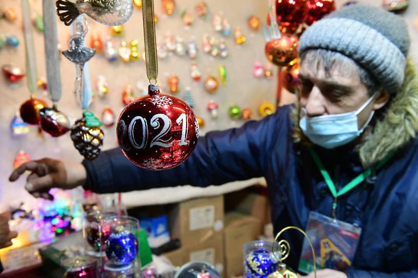 Елочный шар 2021 на фоне продавца новогодних украшений
