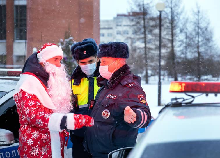 Участник благотворительного автопробега в костюме Деда Мороза общается с сотрудниками ДПС