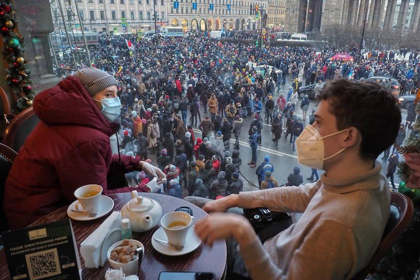 Несогласованные акции в поддержку политика Алексея Навального в центре Петербурга. Посетители кафе наблюдают за маршем протестующих на Невском проспекте