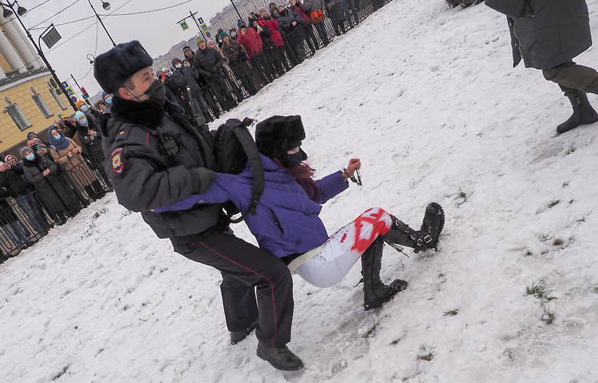 Несогласованная акция в поддержку политика Алексея Навального на Сенатской площади. Сотрудник полиции во время задержания девушки