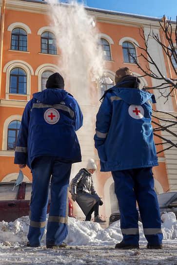Медики наблюдают за сбросом снега с крыши дома в центральной части города