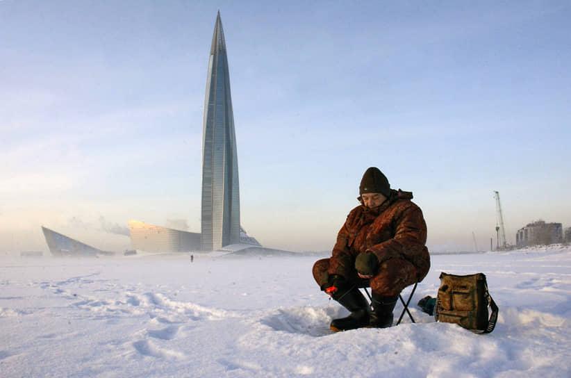 Рыбак ловит рыбу на льду Финского залива на фоне башни Лахта-центра