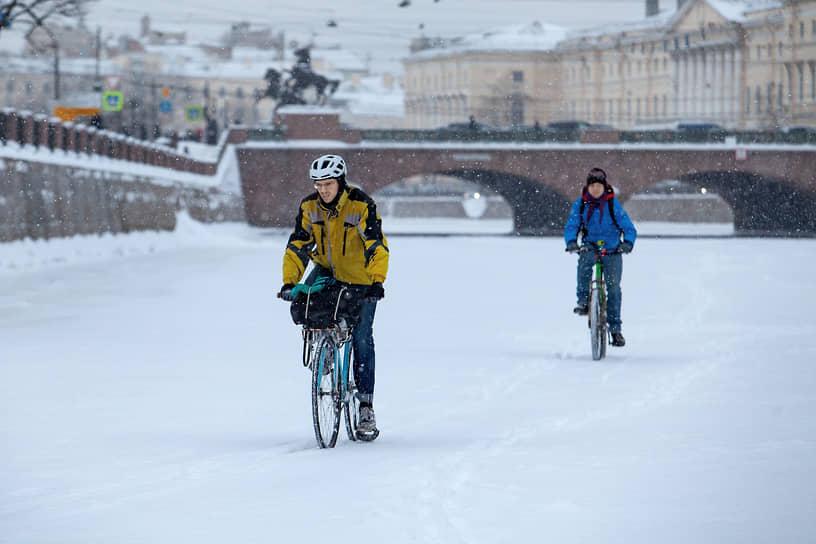 Велосипедисты во время велосипедной прогулки по льду реки Фонтанки