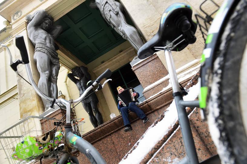 Уличный музыкант играет на ступенях Нового Эрмитажа