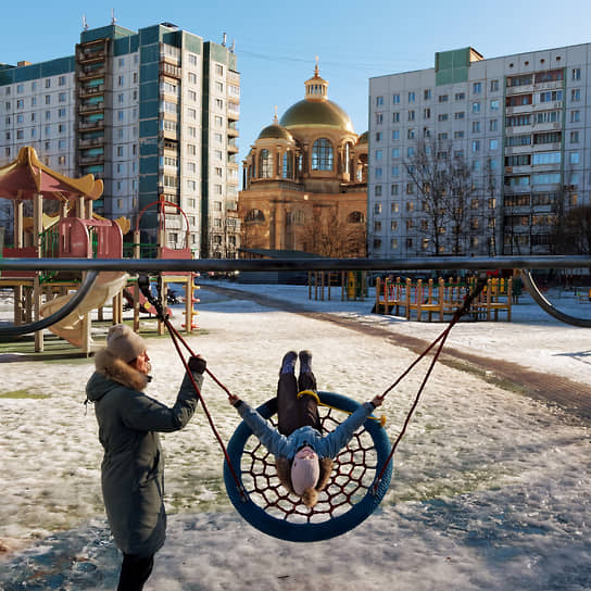 Женщина с ребенком на детской площадке в спальном районе города