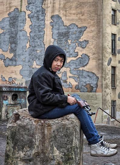Мальчик во дворе с игрушечным автоматом Калашникова