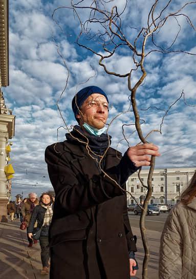 Молодой человек идет по Невскому проспекту с саженцем дерева