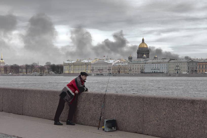 """Мужчина ловит рыбу на фоне дыма от пожара в зданиях компании """"Невская мануфактура"""""""