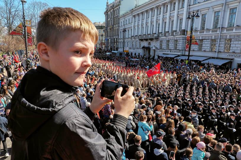 Подросток снимает на смартфон военнослужащих после военного парада на Дворцовой площади